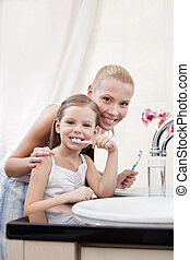Little girl cleans teeth with her mother