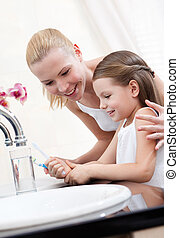 Little girl cleans teeth with her mum