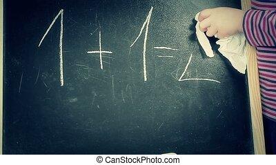 Little girl clear math task from the blackboard