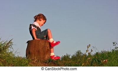 little girl climb on stump