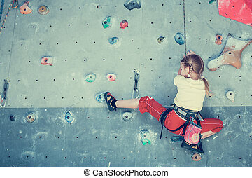 little girl climbing a rock wall indoor