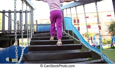 Little girl climbing on stairs at playground - Little girl...