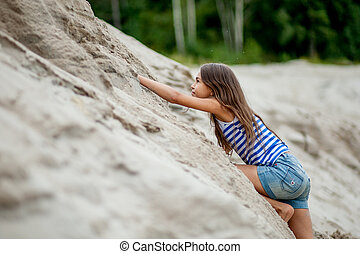 girl climbing on the sand - little girl climbing on the sand...