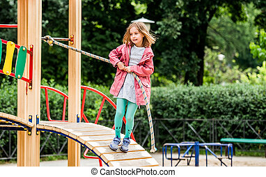 Little girl climbing rope on playground
