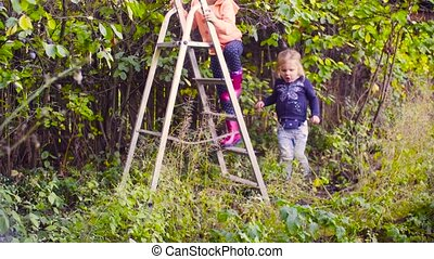 Little girl climbing up a ladder and starting to collect...