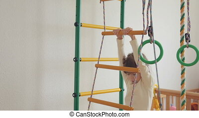Little girl climbing up on wall bars