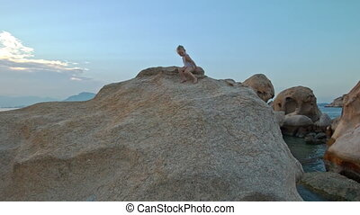 Little Girl Climbs Down Large Rock Top at Sunset on Beach