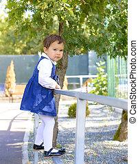 little girl climbs on the railing
