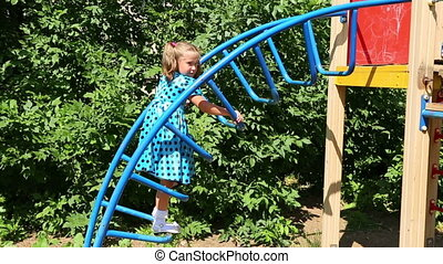 little girl climbs the stairs on the playground
