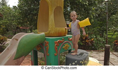 Little Girl Climbs up Water-slide at Swimming Pool at Hotel...