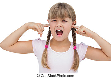 Little girl clogging her ears with her fingers on white...