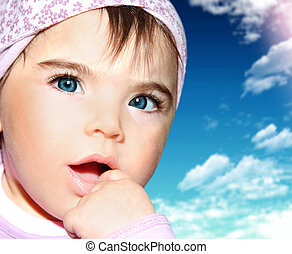 Little girl closeup portrait over sky