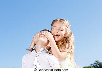 Little girl closing eyes of the boy