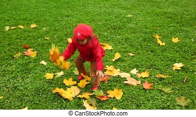 little girl collect and throws up leafs in autumn park