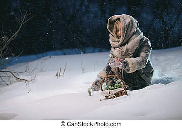 little girl collects in a basket the first flowers under the snow in the winter