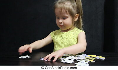 Little girl collects puzzles at the table on a dark gray background