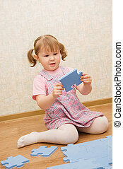 little girl collects puzzles in a room