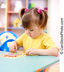 Little girl coloring a picture in preschool