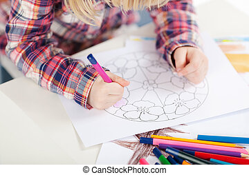 Little girl colouring in a medallion