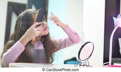 little girl combing her hair doing a hairdo. teen girl puffs...