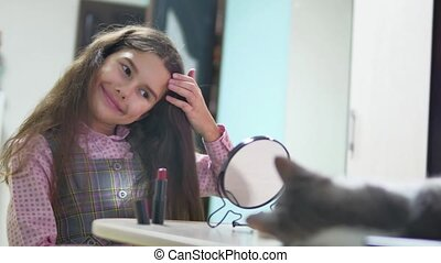 little girl combing her indoor hair doing a hairdo. teen...