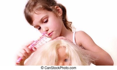Little girl combs dolls hair, isolated