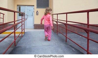 little girl comes to door of apartment block and using entrance door intercom
