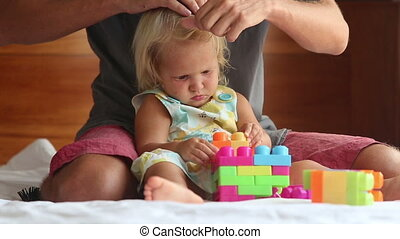 little girl composes toy constructor on sofa - little blonde...