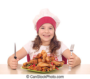 little girl cook with chicken drumstick on plate ready for lunch