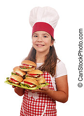 little girl cook with hamburgers on plate