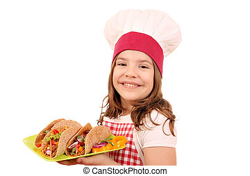 little girl cook with tacos on plate