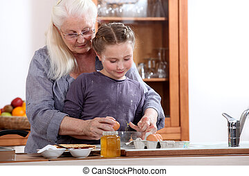 Little girl cooking with grandmother