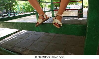 little girl costs on handrail of gazebo among children's...