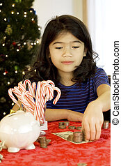Little girl counting money at Christmas
