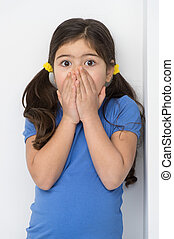 little girl covering face and mouth. nice girl standing...