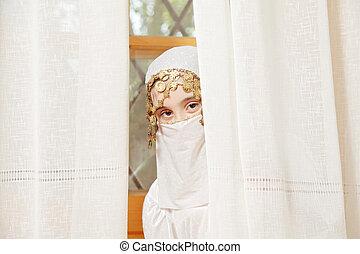 Little girl covering face hiding
