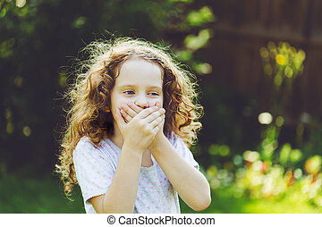 Little girl covering her mouth with her hands. Surprised or ...