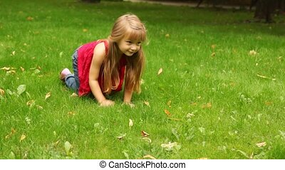 Little girl crawl on all fours on grass