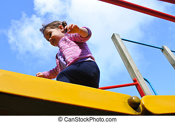 Little girl cross a playground bridge