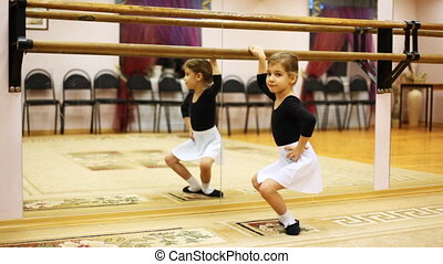 little girl crouches in ballet position while standing sideways to mirror at hall