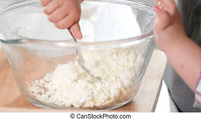 Little girl crumple cottage cheese with a fork in a glass...