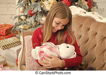 Little girl cuddle cute bunny at Christmas tree. Small girl hold rabbit toy. Little child play with soft toy. Small child happy smiling with present. Best Christmas toy. I love my bunny