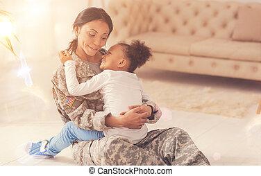 Little girl cuddling her mother on the floor