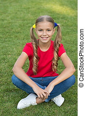 Little girl cute ponytails hairstyle relaxing on green grass, carefree childhood concept