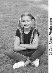 Little girl cute ponytails hairstyle relaxing on green grass, child care concept