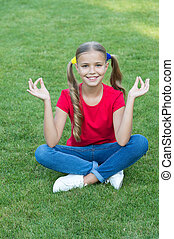 Little girl cute ponytails hairstyle relaxing on green grass, practice meditation concept