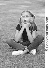 Little girl cute ponytails hairstyle relaxing on green grass, sad day concept