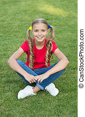 Little girl cute ponytails hairstyle relaxing on green grass, summer vacation concept