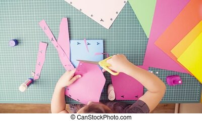 Little girl cutting colored paper with scissors - Rotation....