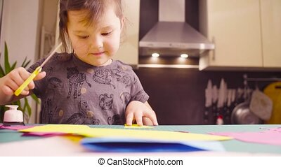 Little girl cutting colored paper with scissors -...